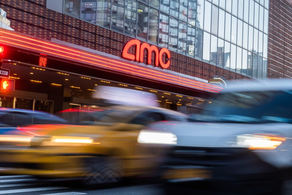 AMC share price: the AMC logo in lights on a busy street