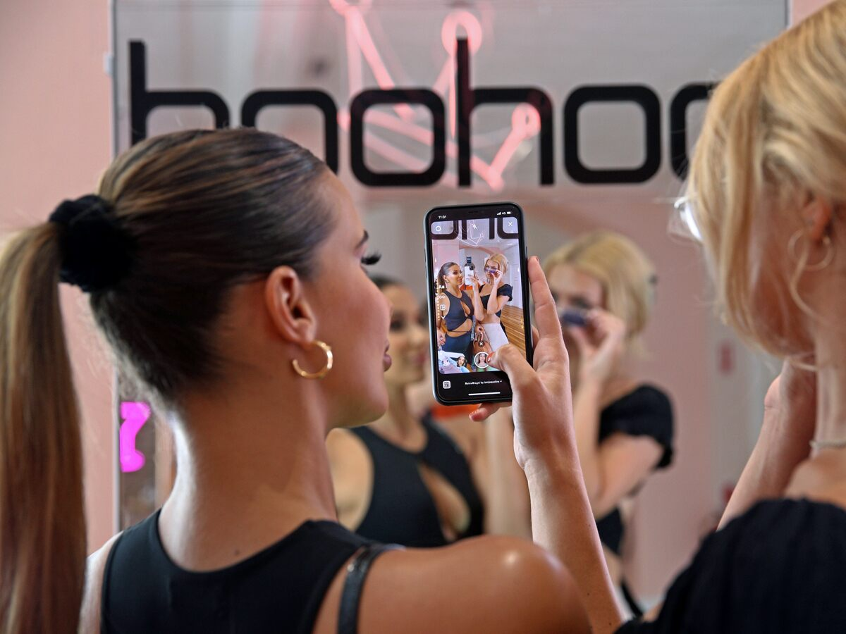 Boohoo share price: A woman takes a photo on her mobile phone at a Boohoo fashion party